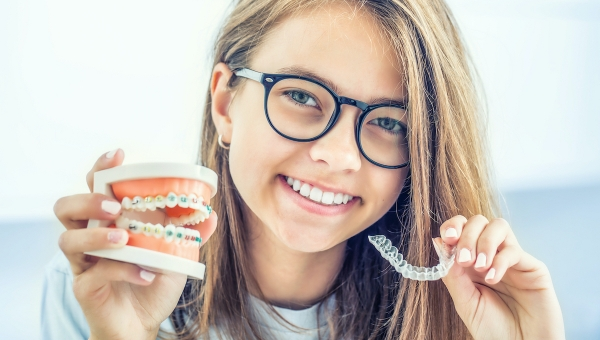 Young girl comparing metal braces with Invisalign