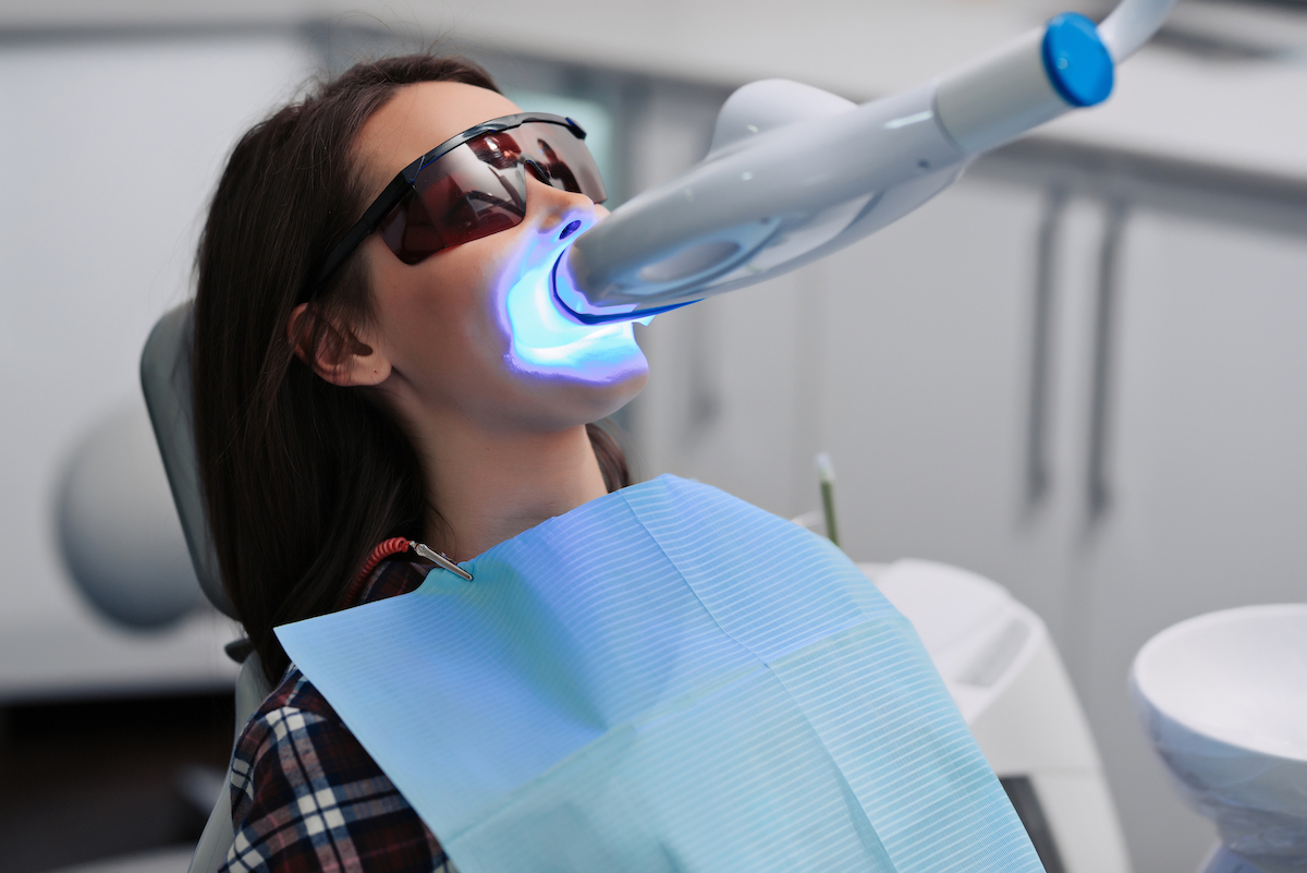 woman getting in-office teeth whitening done at our Houston cosmetic dentist office
